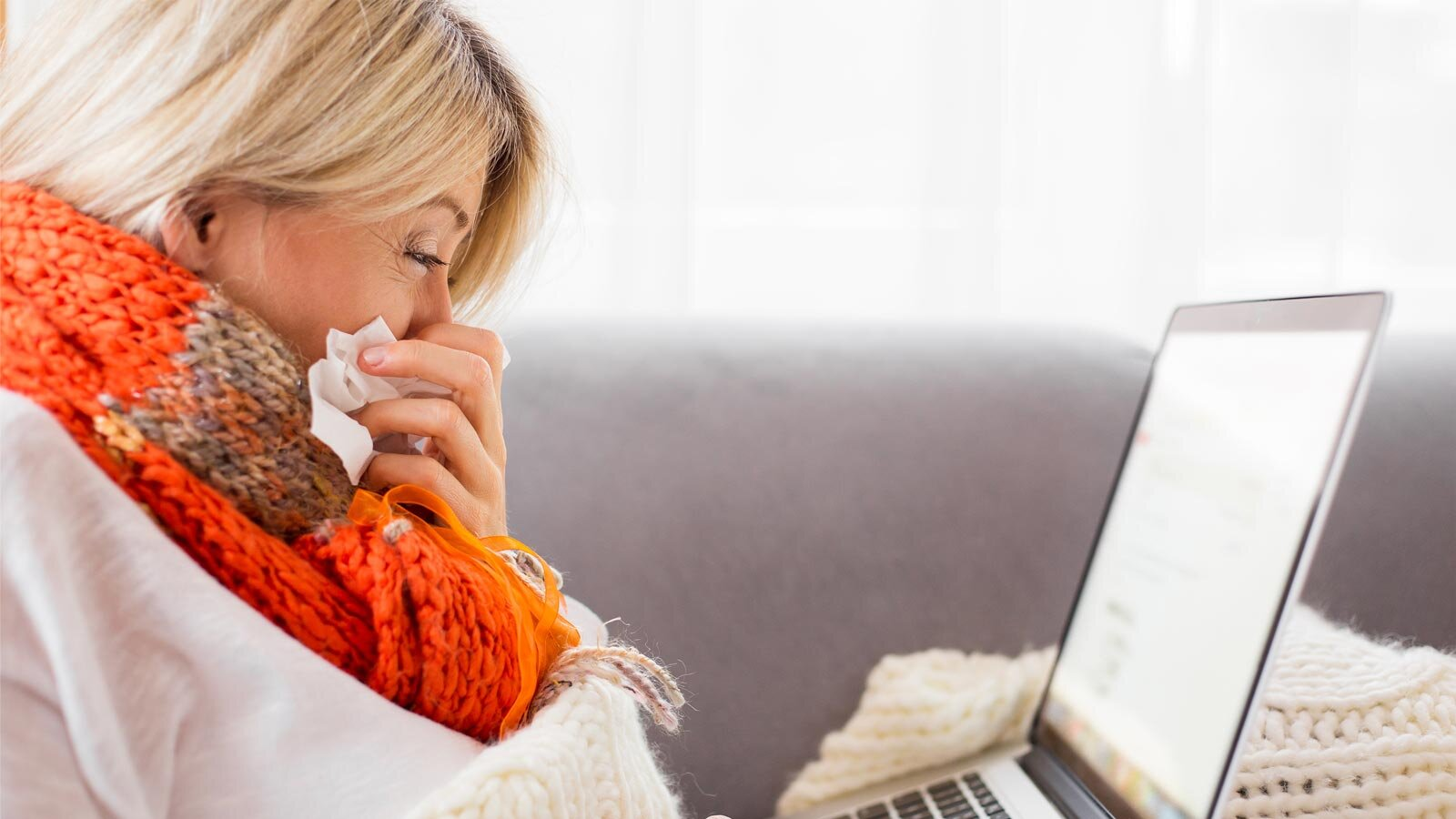 A woman in an orange scarf on a laptop blowing her KC.IsPrimaryLogo.Nose