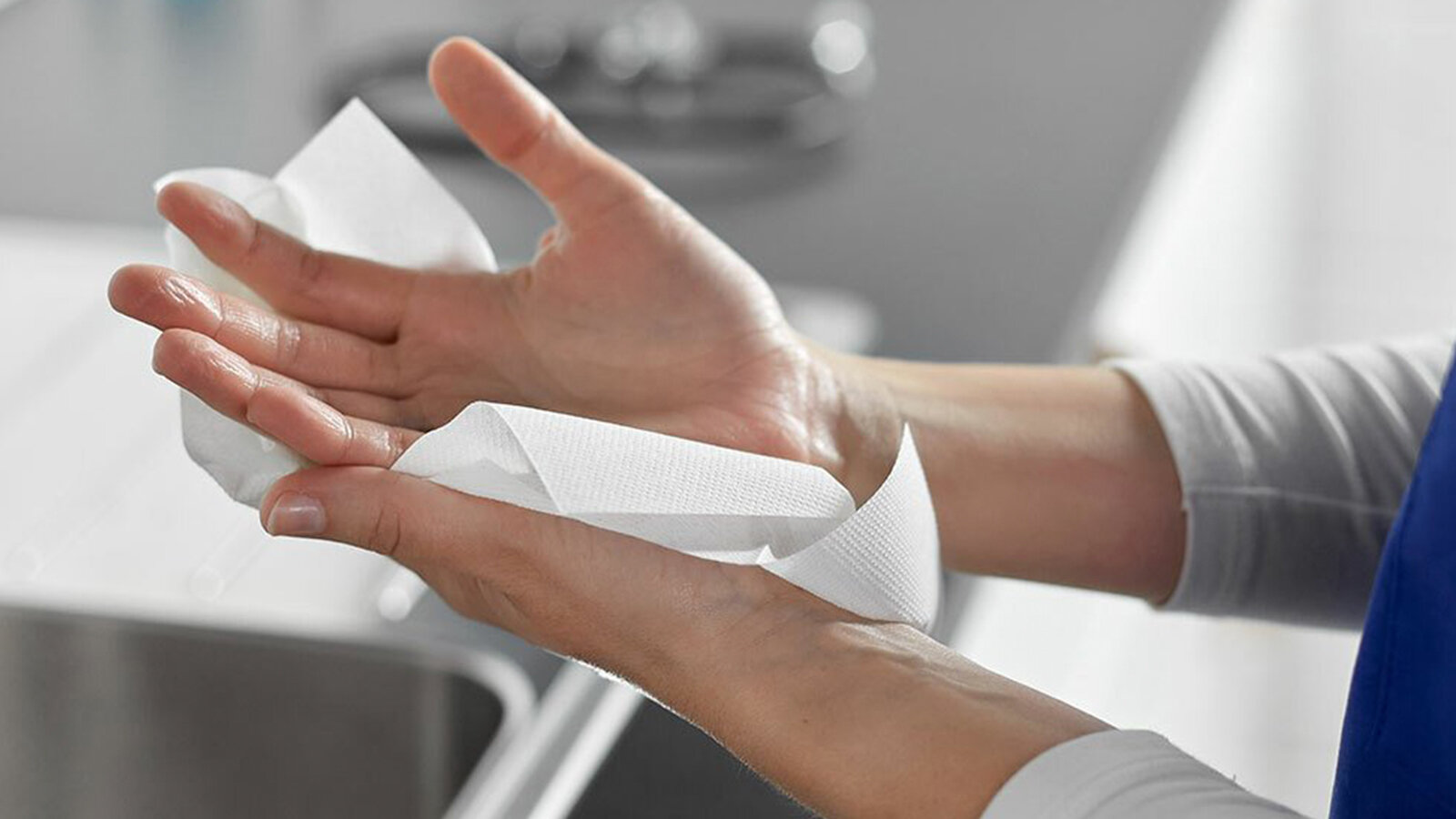 Caucasian drying hands with a white paper hand towel