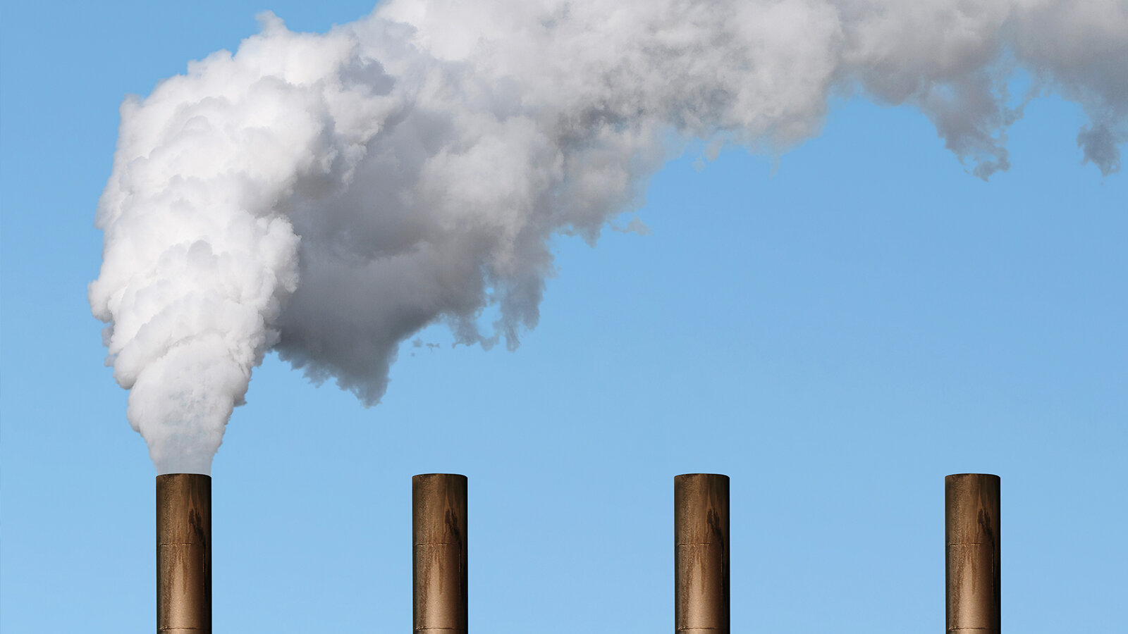 Four industrial smoke stacks with white smoke coming out of one
