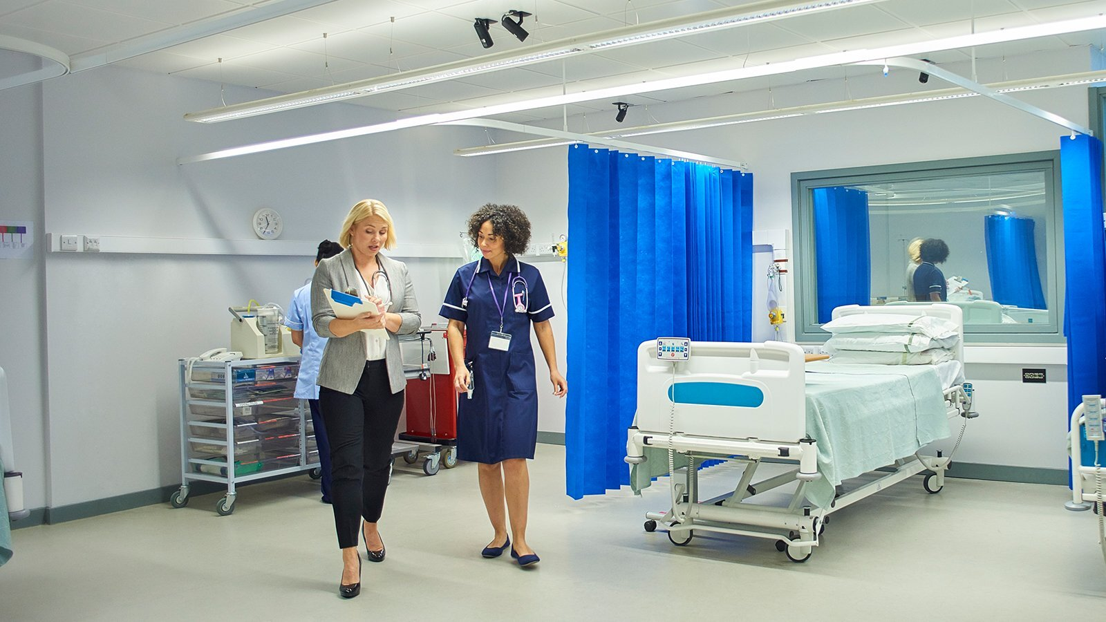 A large hospital room with healthcare professionals and a patient in a hospital bed