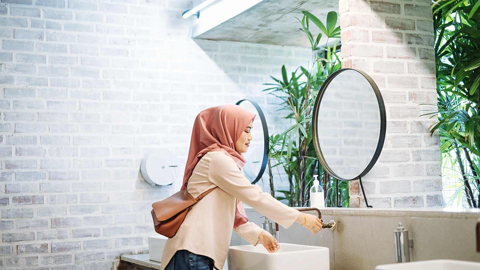 Woman with headscarf using the sink in a restroom.