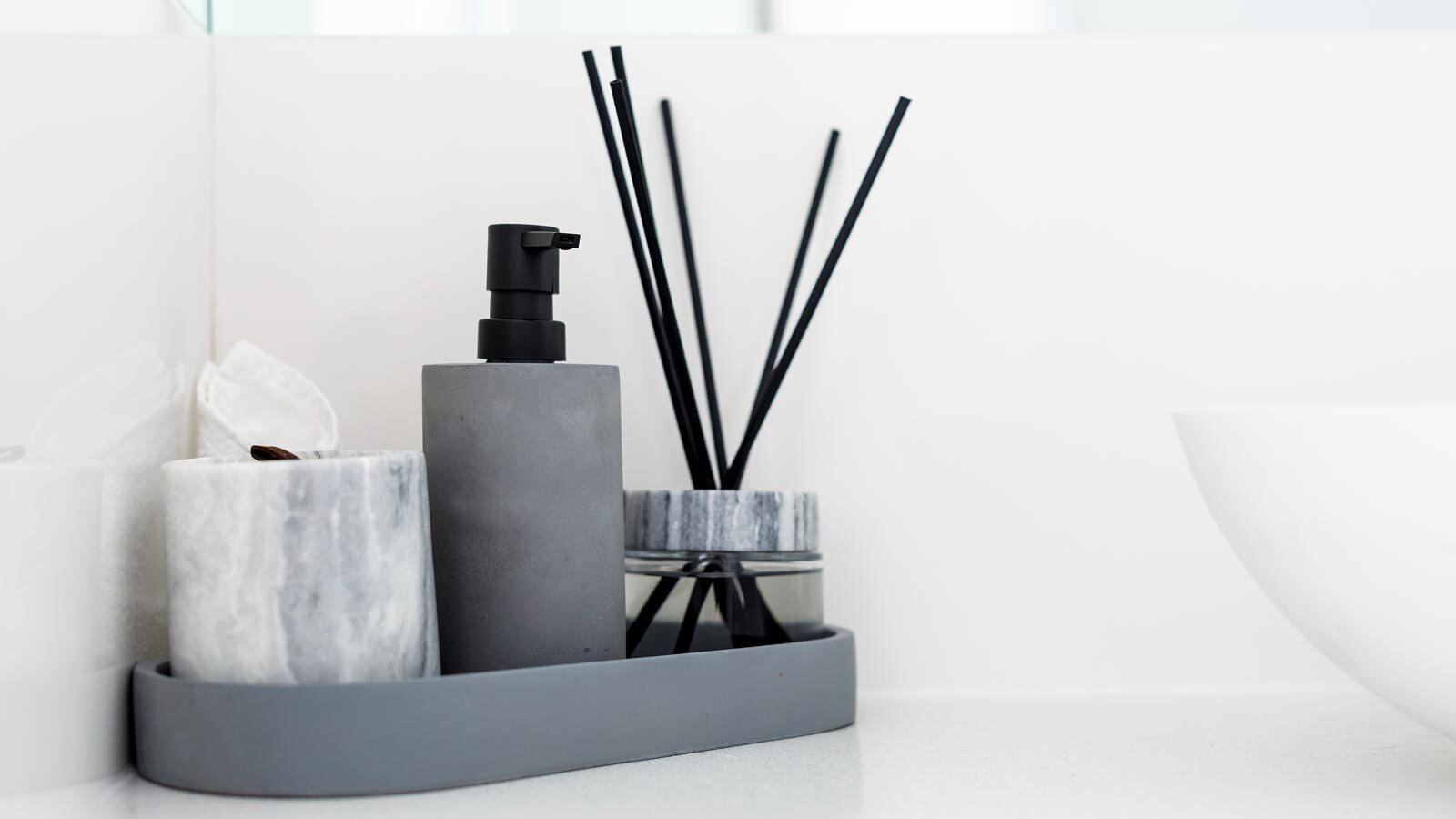 A marble and grey bathroom accessory set featuring a cup, lotion dispenser and oil diffuser