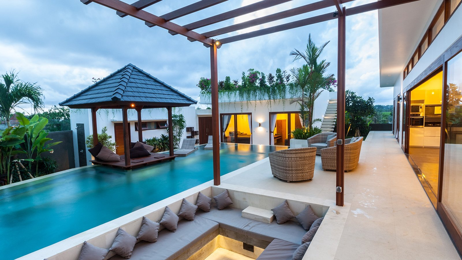 The outside patio of a luxury resort featuring a pool, pergola and outdoor seating