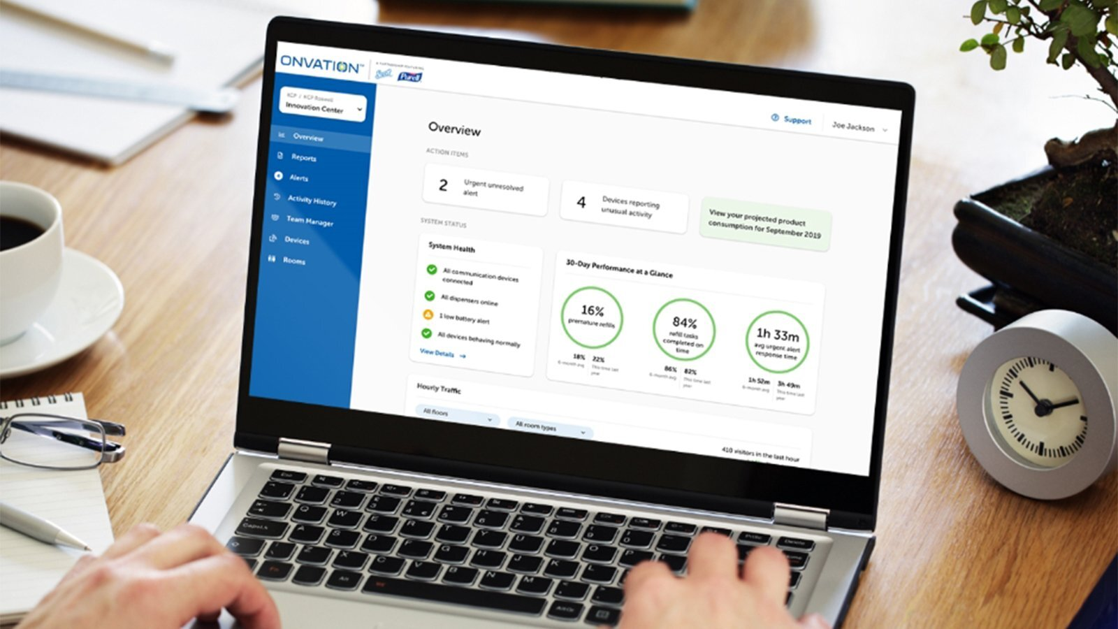 A laptop computer displaying an overview of the Onvation dashboard and an image of a facility manager.